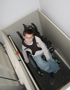 Boy in a wheelchair in an in-home elevator looking up at the camera