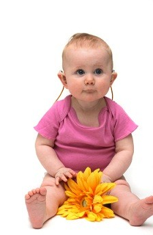 baby wearing hearing aid and holding a flower looking in the direction of the camera