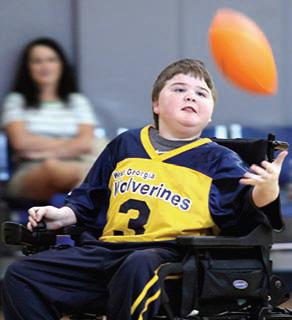 Young boy wearing a jersey and in a motorized wheelchair tosses a football