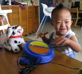 Boy using a simple switch to operate toy dog 2