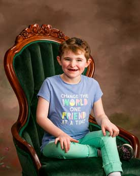 Child with Angelman Syndrome sitting in a large chair and smiling at the camera