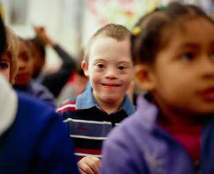Six-year-old boy with Down's syndrome (centre), with fellow pupils at a mainstream school. Down's syndrome is a chromosomal abnormality resulting in mental handicap and a characteristic physical appearance.