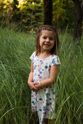 Young girl with standing in tall grass smiling